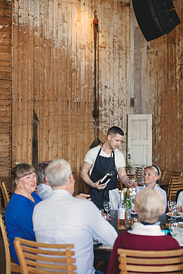 Young waiter serving wine to senior friends at table in restaurant - p426m1506307 by Maskot