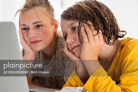 Young boy and teenage sister sharing a laptop, watching in a bedroom - p1100m2300990 by Mint Images