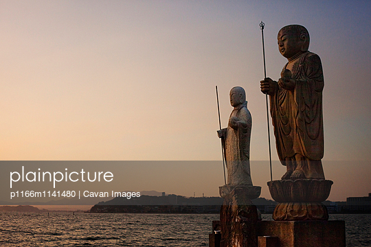 Sculptures by Lake Shinji against clear sky during sunset