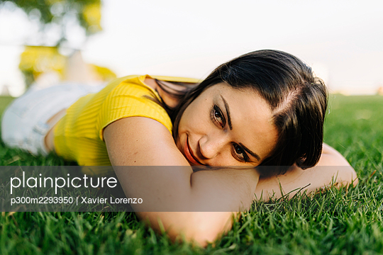Young woman day dreaming while lying in park - p300m2293950 by Xavier Lorenzo