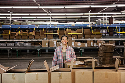 Portrait of an African American female warehouse worker in a large distribution warehouse with products stored in cardboard boxes. - p1100m1575466 by Mint Images