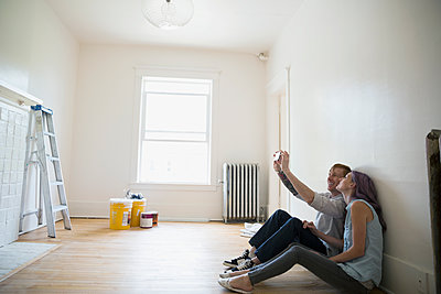 Couple taking selfie in empty new house - p1192m1158276 by Hero Images