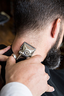 Barber cutting the hair of a man using a vintage hand operated hair clipper - p300m1205229 by Andrés Benitez