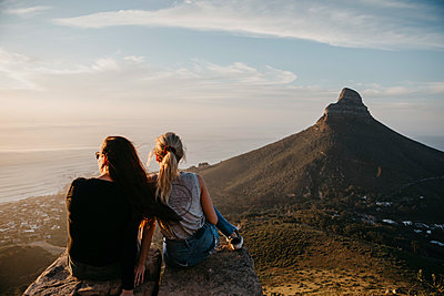 South Africa, Cape Town, Kloof Nek, two women sitting on rock at sunset - p300m2080819 by letizia haessig photography