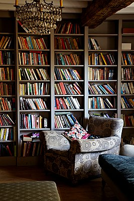 Armchair in front of bookcase in East Sussex farmhouse,  England,  UK. - p349m959368 by Alun Callender