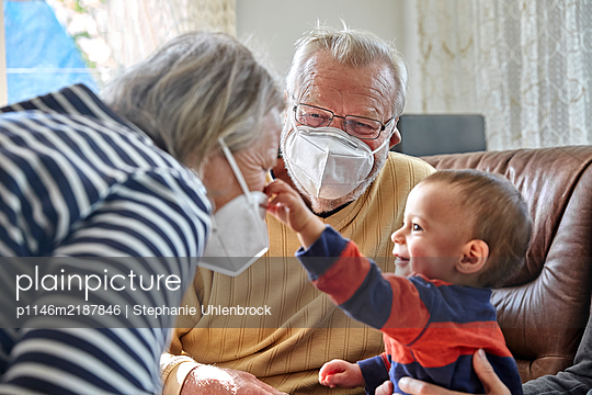 Grandparents with face mask and grandson, portrait - p1146m2187846 by Stephanie Uhlenbrock