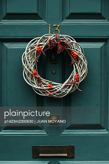 Christmas wreath hanging from the green frontdoor - p1423m2300630 by JUAN MOYANO