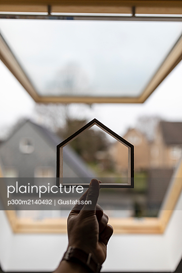 Hand holding wooden house model against window - p300m2140492 by Gustafsson