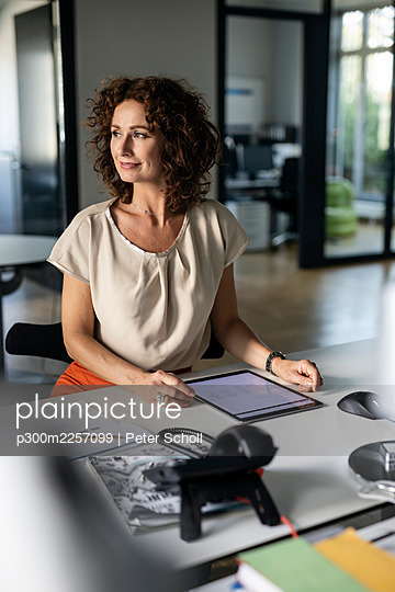 Businesswoman with digital tablet looking away while sitting at desk in office - p300m2257099 by Peter Scholl