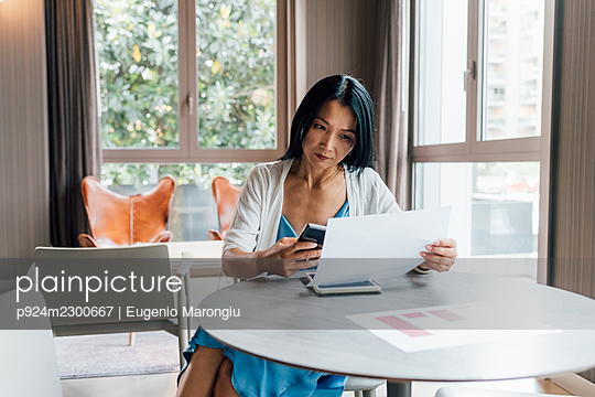 Italy, Businesswoman working at table in creative studio - p924m2300667 by Eugenio Marongiu