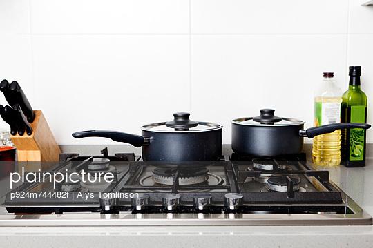 Saucepans on gas hob - p924m744482f by Alys Tomlinson