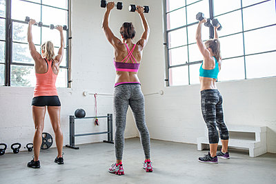 Full length of female athletes lifting dumbbells in health club - p1166m1422986 by Cavan Images