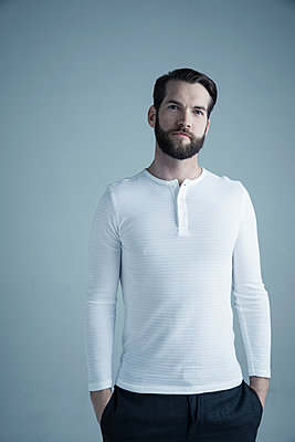 Portrait confident brunette Caucasian young man with beard wearing white henley - p1192m1213165 by Hero Images