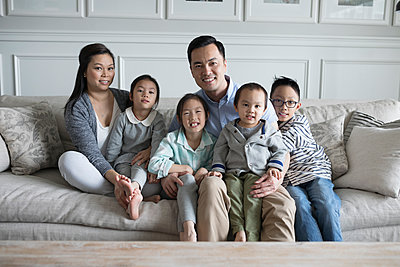 Portrait smiling young family on living room sofa - p1192m1231395 by Hero Images