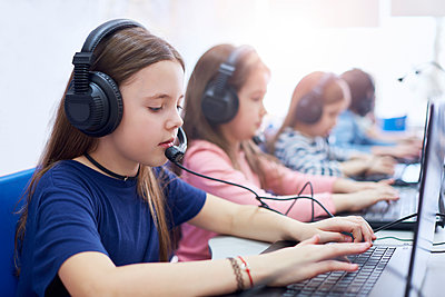 Pupils wearing headsets and using laptops in school - p300m1587245 by gpointstudio