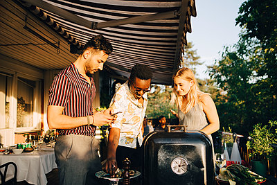 Friends talking while enjoying grilled food at dinner party in back yard - p426m2097388 by Maskot