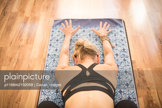 A girl in child's pose during yoga. - p1166m2192058 by Cavan Images