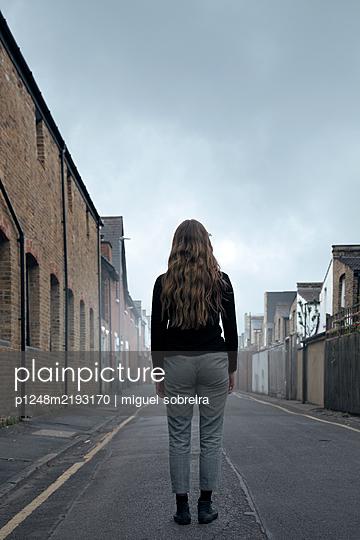 Rückansicht einer jungen Frau in einer verlassenen Straße - p1248m2193170 von miguel sobreira