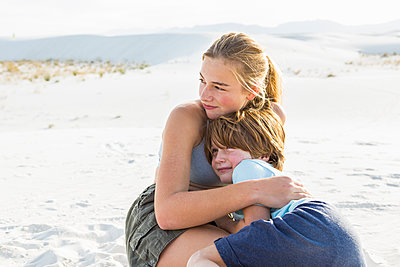A teenage girl embracing her brother,  - p1100m2164772 by Mint Images