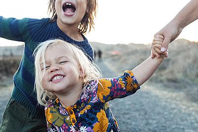 Cropped view of joyful siblings by road in natural park - p1166m2095122 by Cavan Images