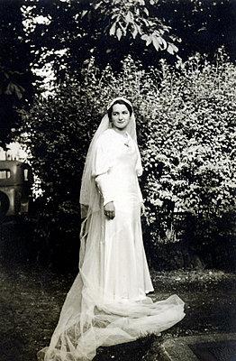 Bride in wedding dress in the garden - p1541m2172495 by Ruth Botzenhardt
