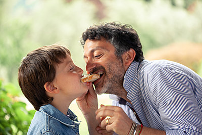 Boy and father eating same slice of bread - p429m2200737 by Sofie Delauw