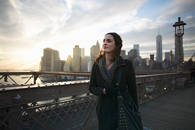 Young woman strolling on Brooklyn bridge, New York, USA - p924m911091f by Chad Springer
