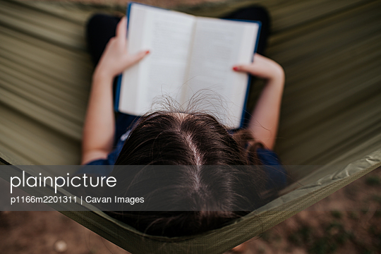 Center overhead frame of teen girl reading in hammock - p1166m2201311 by Cavan Images