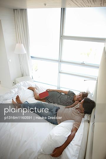 Paar liegt auf einem Bett in einem Hotelzimmer, Hotel Sofitel Vienna Stephansdom, Wien, Österreich - p1316m1160591 von Hauke Dressler