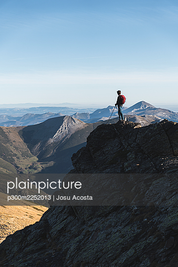 Male hiker exploring while standing on hill against clear sky - p300m2252013 by Josu Acosta