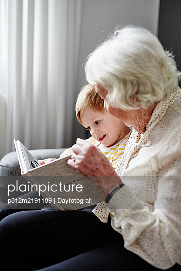 Grandmother reading book to grandson - p312m2191189 by Dayfotografi