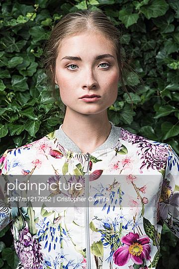 Junge Frau mit geblümtem Kleid - p947m1217252 von Cristopher Civitillo