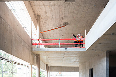 Two men wearing safety vests talking in building under construction - p300m1459936 by Daniel Ingold