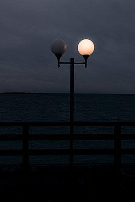 Straßenlaternen am Meer in der Nacht - p354m1564354 von Andreas Süss