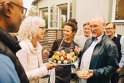 Smiling senior women and men enjoying garden party - p426m2194894 by Maskot