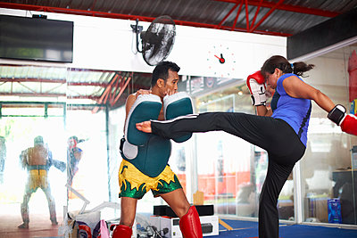 Mature woman practicing kickboxing with male trainer in gym - p429m1547755 by Peter Muller