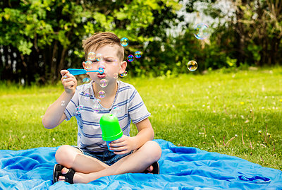 A young boy blowing bubbles and sitting on a blanket in a city park during a family outing on a warm sunny day; Edmonton, Alberta, Canada - p442m2039411 by LJM Photo