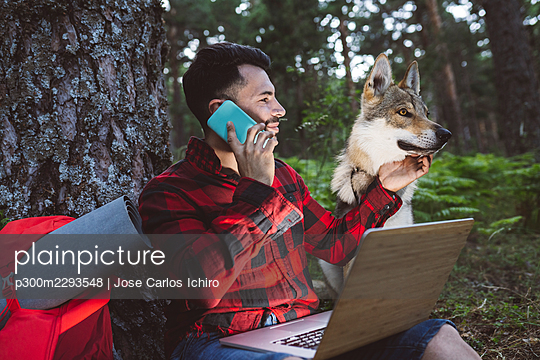Man with laptop talking on mobile phone while sitting by dog in forest - p300m2293548 by Jose Carlos Ichiro