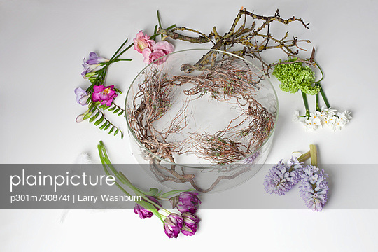 Flowers lying on a table around a glass bowel vase - p301m730874f by Larry Washburn