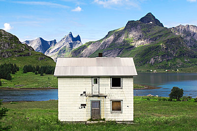 Abandoned white house on grass against lake and mountains - p1025m789351f by Vidar Askland