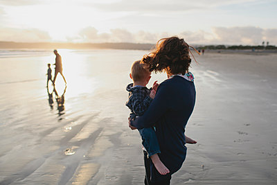 Side view of mother carrying boy looking at family walking at beach - p1166m1210261 by Cavan Images