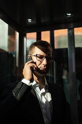 Serious businessman speaking on smartphone in hotel - p1166m2234367 by Cavan Images