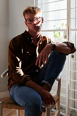 Young man with glasses on a chair, portrait - p1640m2254621 by Holly & John
