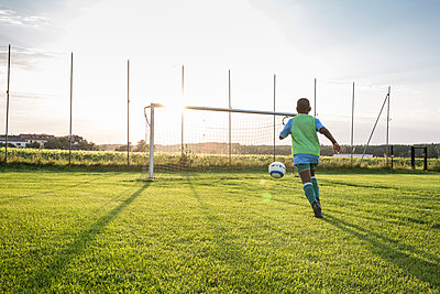 Young football player on football ground at sunset - p300m1581660 by Fotoagentur WESTEND61