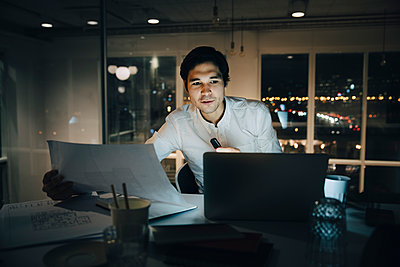 Confident businessman holding paper while looking at laptop in office - p426m2194830 by Maskot