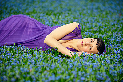 Woman lying on a field of flowers - p5560153 by Wehner