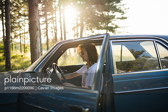 Woman sitting in a parked  broken car. - p1166m2200090 by Cavan Images