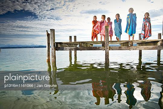 Kinder in Handtücher gewickelt auf einem Steg, Starnberger See, Oberbayern, Bayern, Deutschland - p1316m1161066 von Jan Greune