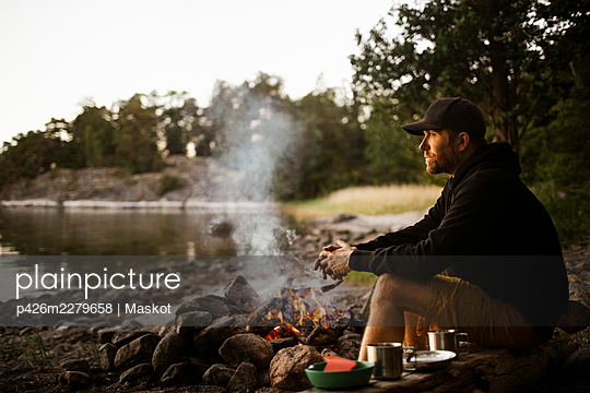 Side view of thoughtful man looking away while sitting by campfire at lakeshore - p426m2279658 by Maskot