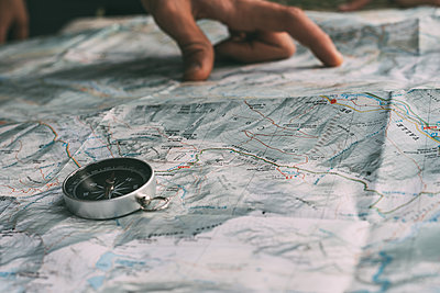 Planning the route on a map and a compass - p1166m2189861 by Cavan Images